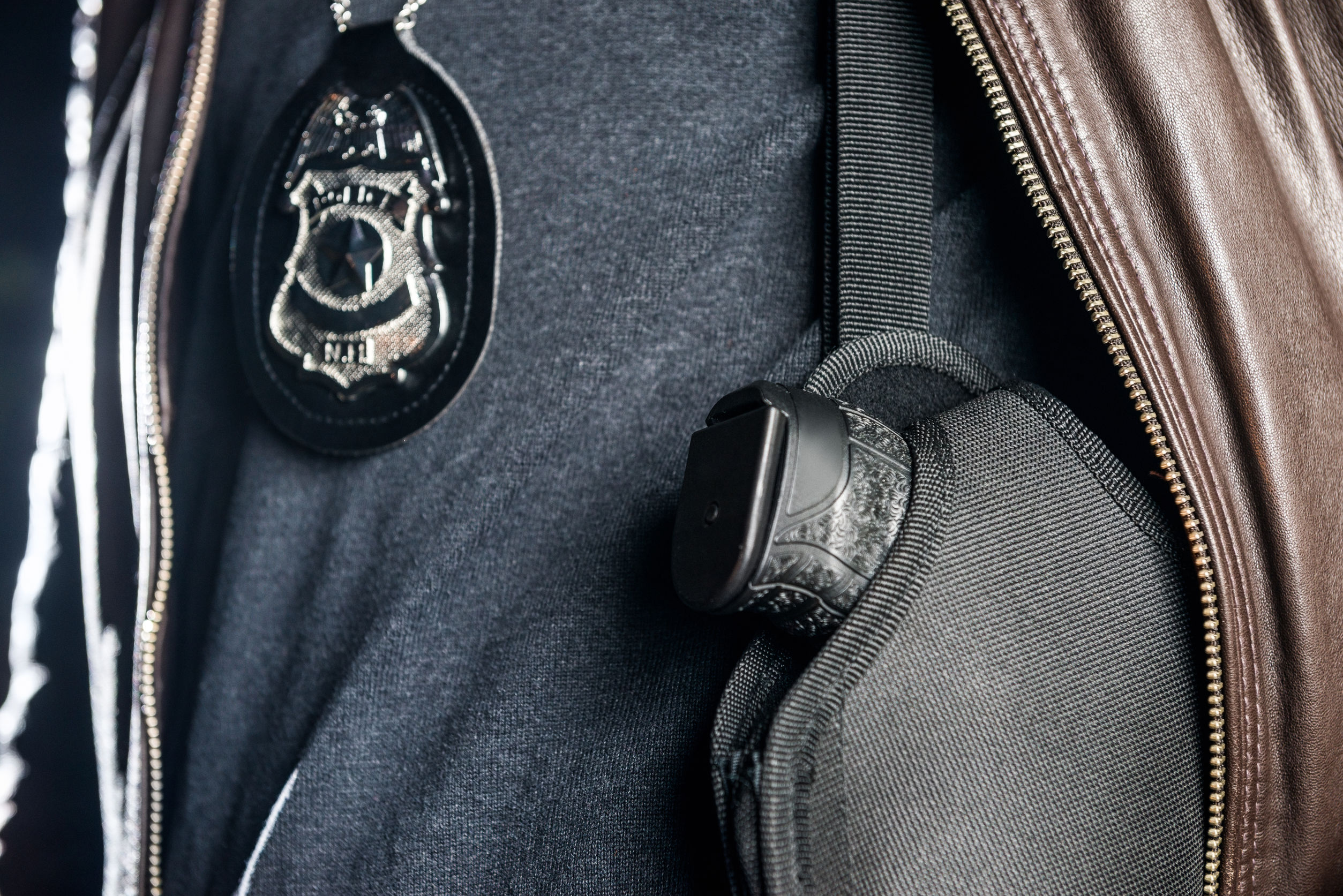 76594265 – closeup of police officer with badge and gun